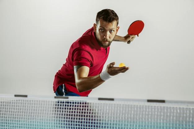 Antwoord. jonge man speelt tafeltennis op witte muur. model speelt pingpong. concept van vrijetijdsbesteding, sport, menselijke emoties in gameplay, gezonde levensstijl, beweging, actie, beweging.