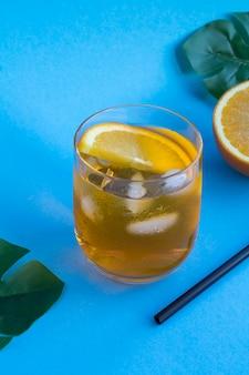 Aperol spritz cocktail in glas op de blauwe tropische achtergrond. locatie verticaal. kopieer ruimte.