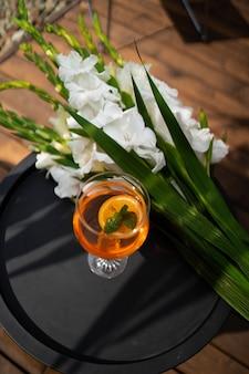 Aperol spritz cocktail in glas op tafel. italiaanse alcoholische cocktail en witte bloemen die op houten achtergrond wordt geïsoleerd. oranje cocktail. barmenu.