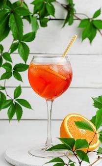 Aperol spritz cocktail met sinaasappel op witte houten ondergrond.