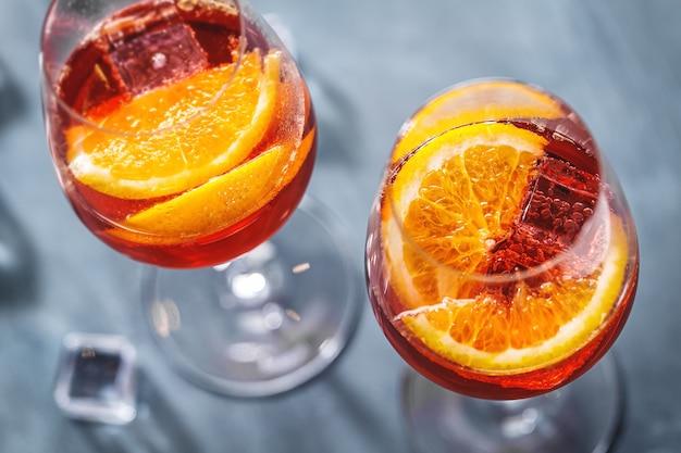 Aperol spritz cocktail met stukjes sinaasappel geserveerd in glazen. detailopname