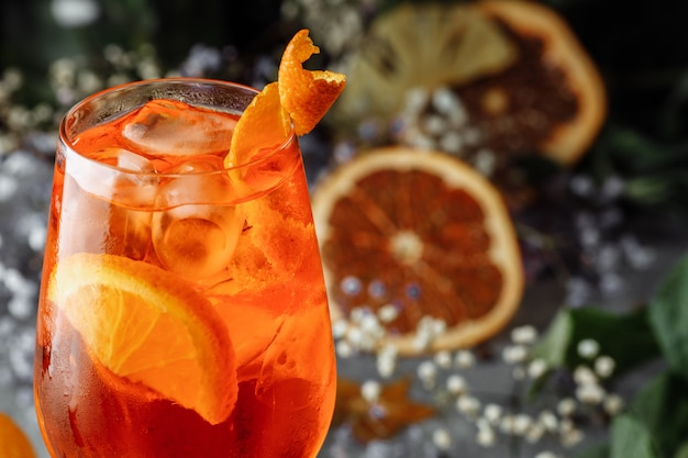 Aperol spritz cocktail op een grijze betonnen achtergrond. een glas aperol spritz met stukjes sinaasappel. zomer cocktail in een glas