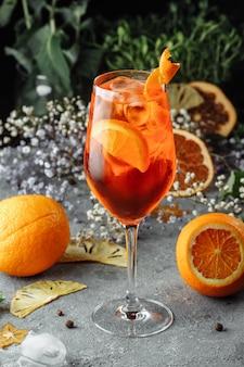 Aperol spritz cocktail op een grijze betonnen tafel. een glas aperol spritz met stukjes sinaasappel. zomercocktail in een glas.