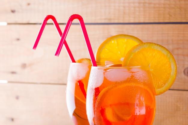 Aperol spritz cocktail op houten planken. twee glazen met zomer alcoholische cocktail met stukjes sinaasappel. italiaanse cocktail