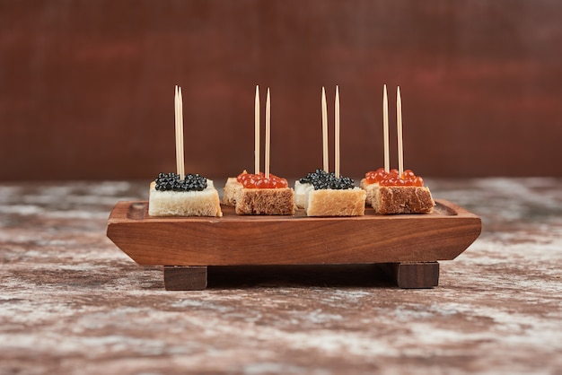Apetizer toast met kaviaar op een houten bord.