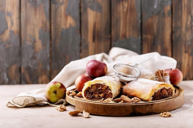 Apfelstrudel geserveerd met verse appels, kaneelstokjes en walnoten op witte textuur achtergrond