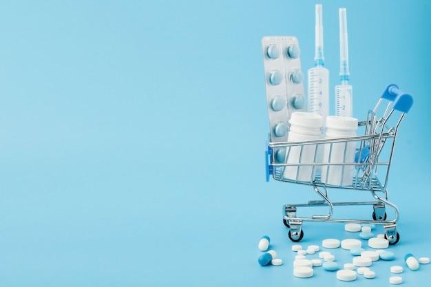 Apotheek geneeskunde. winkelwagen met pillen en medische benodigdheden.