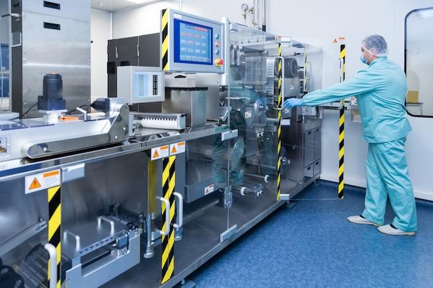 Apotheek industrie man fabrieksarbeider in beschermende kleding in steriele arbeidsomstandigheden die op farmaceutische apparatuur