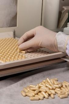 Apotheekprofessional die een inkapselingsplaat gebruikt voor de productie van homeopathische of allopathische middelen.