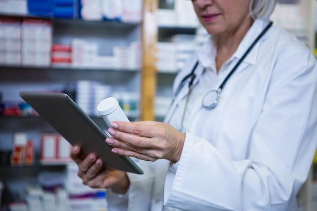 Apotheker die digitale tablet houden terwijl het controleren van geneeskunde