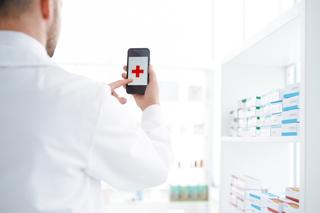 Apotheker die een smartphone gebruikt in zijn apotheek