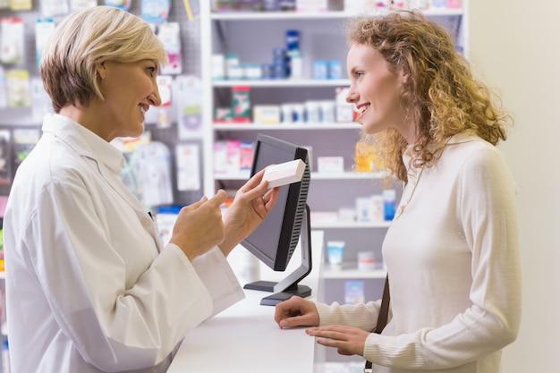 Apotheker die geneeskundedoos houdt die aan klant spreekt