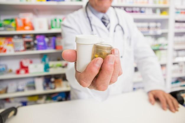 Apotheker die medicijnen op zijn hand voorstelt