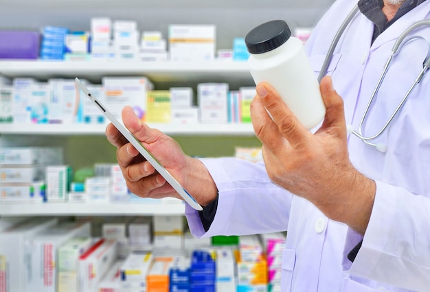 Apotheker die medicijnfles en computertablet houdt voor het invullen van recept