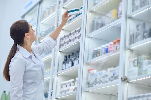 Apotheker die naar medicijnen reikt in de schappen van de apotheek