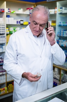 Apotheker die op mobiele telefoon spreekt terwijl het controleren van geneeskunde