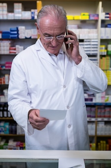 Apotheker die op mobiele telefoon spreken terwijl het controleren van voorschrift