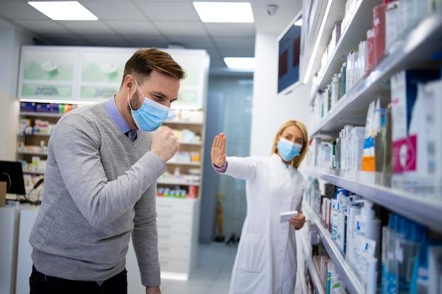 Apotheker doet een stap achteruit terwijl zieke klant hoest en coronavirus verspreidt in apotheekwinkel