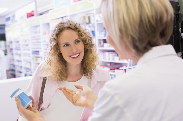 Apotheker en haar klant praten over medicatie