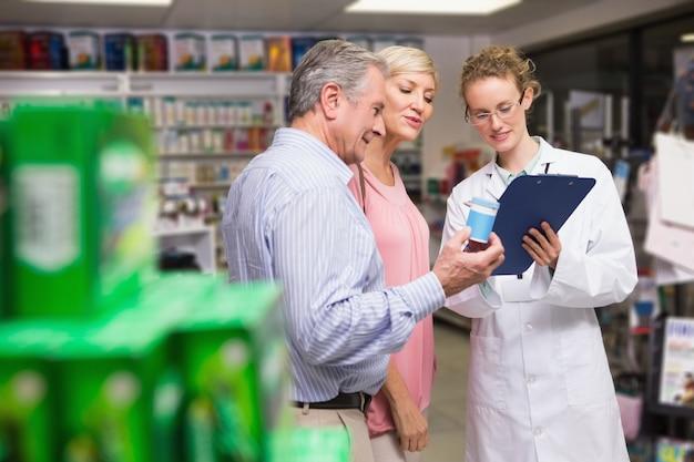 Apotheker en haar klanten praten over medicatie