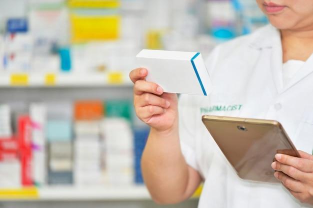 Apotheker houden geneeskunde doos en touchpad voor zoekbalk tentoongesteld in apotheek drogisterij planken achtergrond. online medisch concept.