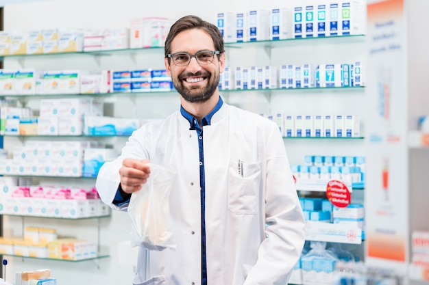 Apotheker in apotheek die geneesmiddelen in zak verkoopt