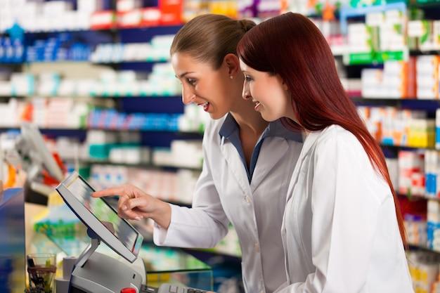 Apotheker met assistent in de apotheek