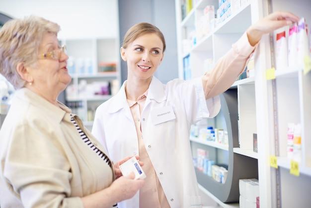 Apotheker met cliënt die geneesmiddelen onderzoekt