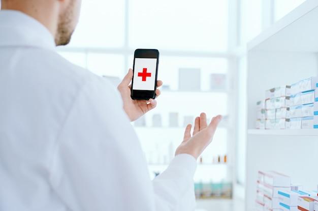 Apotheker met een smartphone die bij de plank met medicijnen staat