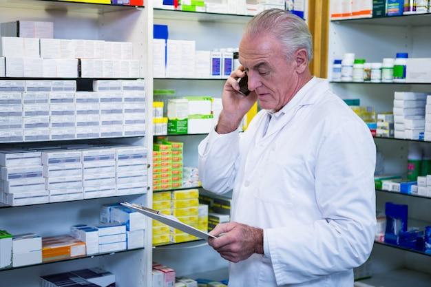 Apotheker praten op mobiele telefoon tijdens het controleren van medicijnen