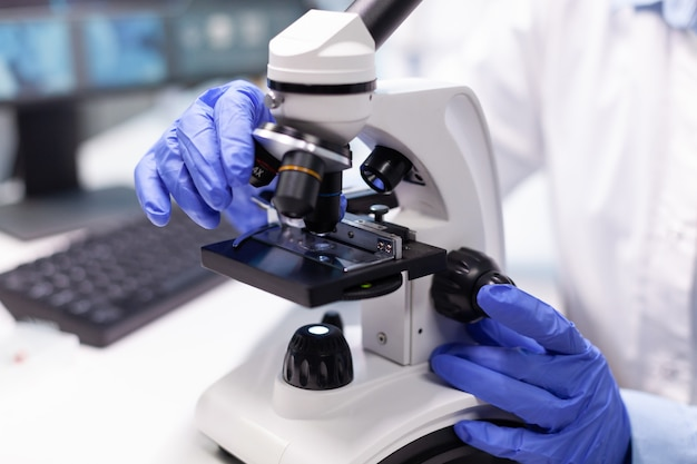 Apotheker vrouw arts analyseert coronavirus dna-test met behulp van medische microscoop