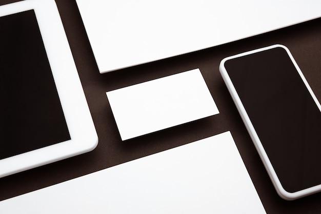 Apparaat met leeg scherm zwevend boven bruine achtergrond. telefoon, tablet en kaarten. modern model in kantoorstijl voor reclame. lege witte copyspace voor ontwerp, zaken en financiënconcept.