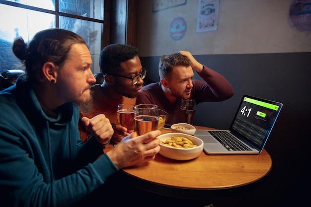 Apparaatscherm met applicatie voor weddenschappen en score. apparaat met wedstrijdresultaten op scherm, opgewonden fans op achtergrond tijdens wedstrijd.