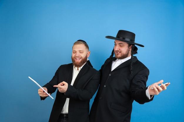 Apparaten gebruiken, lachen. portret van een jonge orthodoxe joodse mannen geïsoleerd op blauwe muur. purim, zaken, festival, vakantie, viering pesach of pesach, jodendom, religie concept.