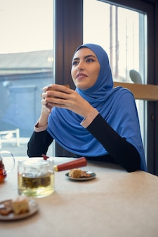 Apparaten gebruiken. mooie arabische vrouw bijeen in café of restaurant, vrienden of zakelijke bijeenkomst. samen tijd doorbrengen, praten, lachen. moslim levensstijl. stijlvolle en vrolijke modellen met make-up.