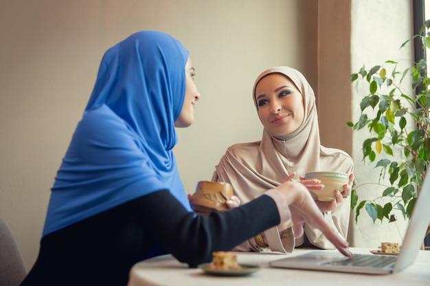 Apparaten gebruiken. mooie arabische vrouwen ontmoeten elkaar in café of restaurant, vrienden of zakelijke bijeenkomst. samen tijd doorbrengen, praten, lachen. moslim levensstijl. stijlvolle en vrolijke modellen met make-up.