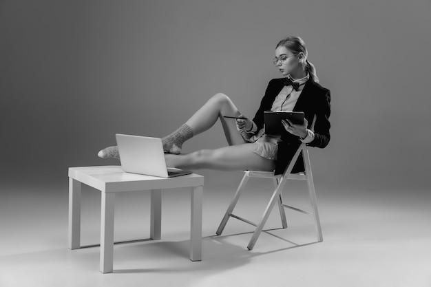 Apparaten. jonge modieuze, stijlvolle vrouw met jas en sokken die vanuit huis werken. mode tijdens isolatie vanwege de pandemie van het coronavirus. half zakelijk en half huisstijl. zwart en wit.