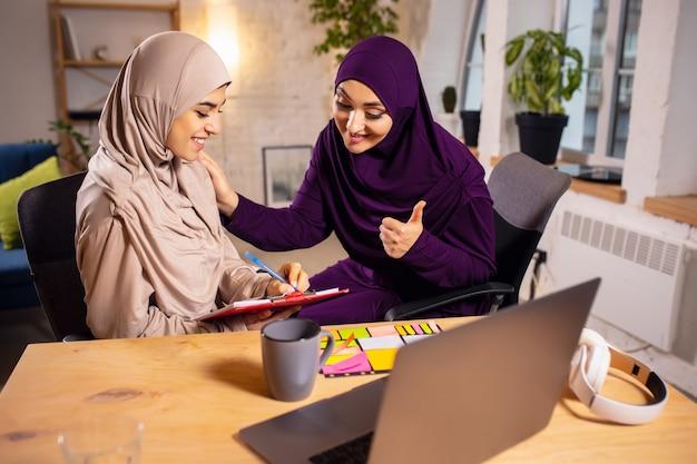 Apparaten, techniek. gelukkige en jonge twee moslimvrouwen thuis tijdens de les, studeren in de buurt van computer, online onderwijs. cultuur, tradities, moderne mensen. kijken op pc-monitor, winkelen of praten.