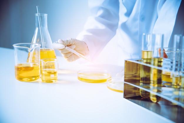 Apparatuur en wetenschap experimenten olie gieten wetenschapper met reageerbuis geel onderzoek naar laboratorium.