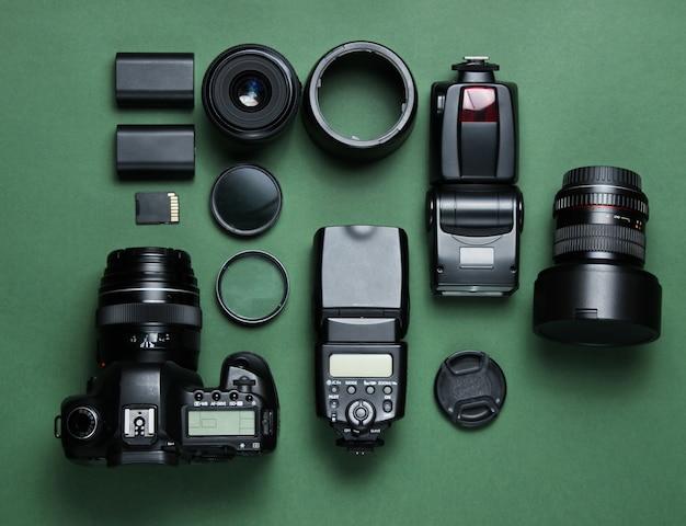 Apparatuur professionele fotograaf op groene tafel. camera, lenzen, flitsers, lichtfilters.