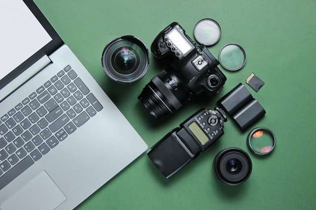 Apparatuur professionele fotograaf op groene tafel. laptop, camera, lenzen, flitsers, lichtfilters.