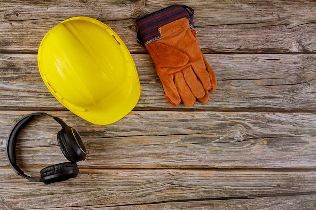 Apparatuur veiligheidsnorm constructie veiligheid oorbeschermers lederen veiligheidshelm beschermende handschoenen op houten tafel