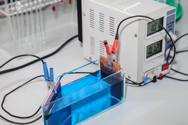 Apparatuur voor elektrolyse in chemisch laboratorium. reagentia en apparaat voor het leveren van stroom op laboratoriumtafel voor experimenten. montage en diverse erlenmeyers en reageerbuisjes in het interieur