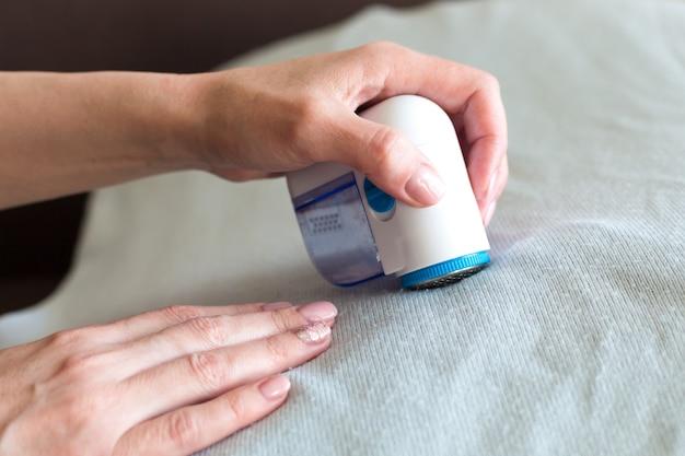 Apparatuur voor het verwijderen van pellets uit kleding in de handen van een vrouw, close-up.