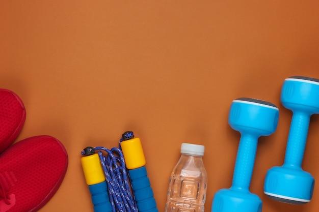 Apparatuur voor training op bruine achtergrond. sportschoenen, springtouw, halters, fles water. plat lag stijl. kopieer ruimte