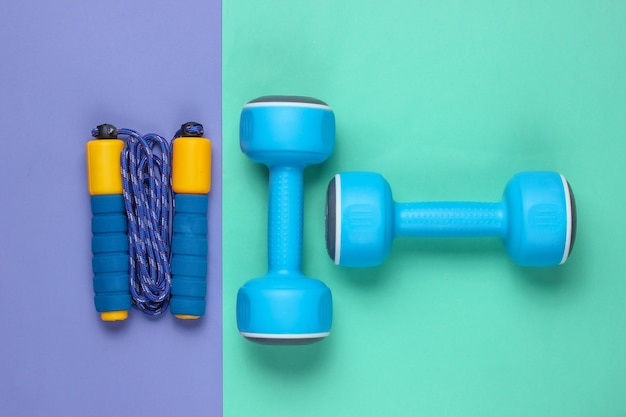 Apparatuur voor training op gekleurde achtergrond. springtouw, halters. plat lag stijl. kopieer ruimte
