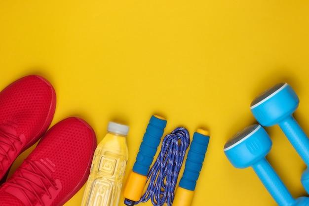Apparatuur voor training op gele achtergrond. sportschoenen, springtouw, halters, fles water. plat lag stijl.