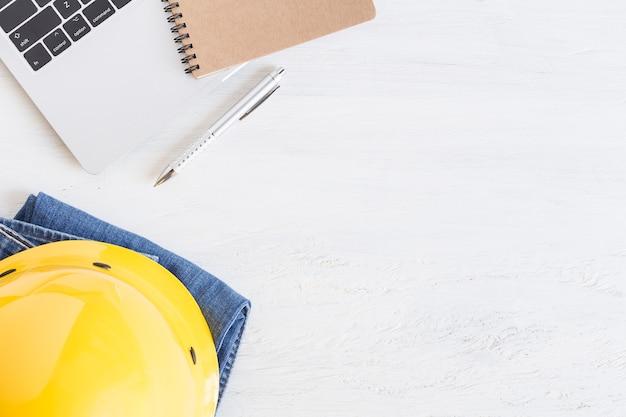 Apparatuur werkt op witte houten vloer, gele helm en notebook