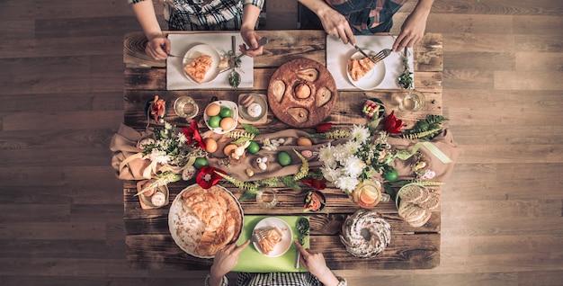 Appartement-feest van vrienden of familie aan de feestelijke tafel met konijnenvlees, groenten, taarten, eieren, bovenaanzicht.