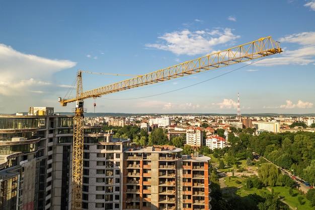 Appartement of kantoor hoog gebouw in aanbouw. bakstenen muren, glazen ramen, steigers en betonnen pilaren.